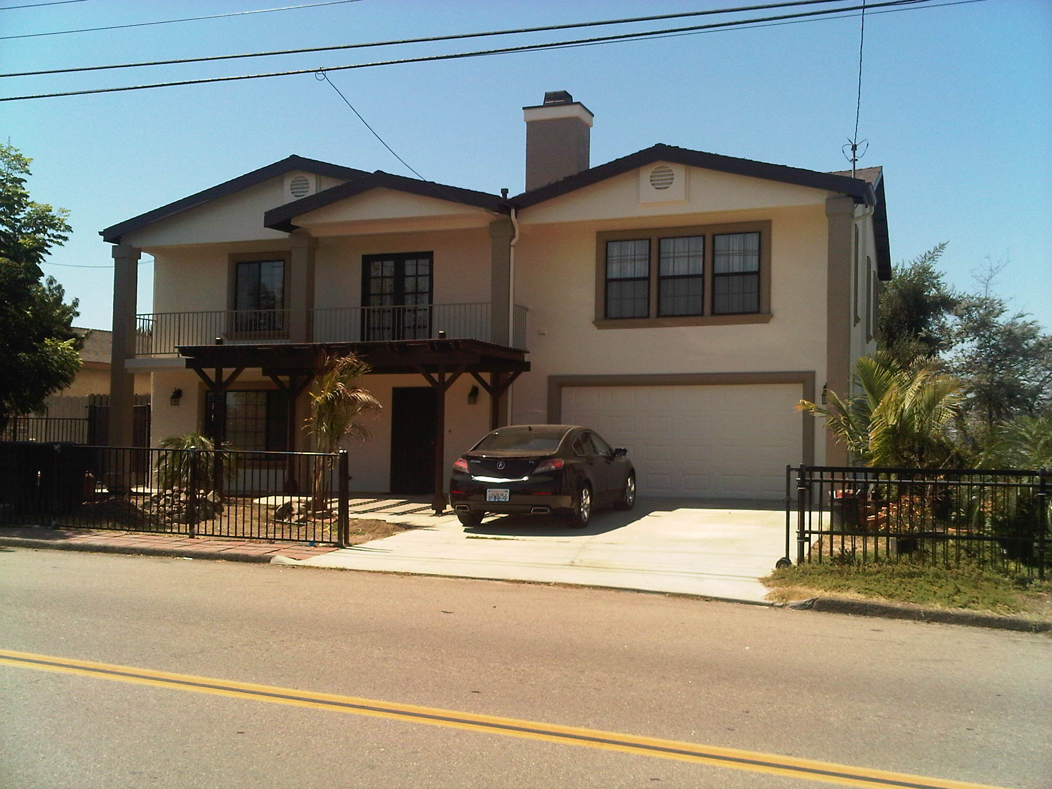 Two story house with new stucco siding color coat is white
